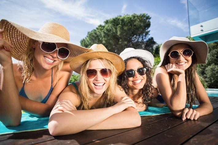 Happy friends enjoying at the swimming pool iStock-693300662.jpg