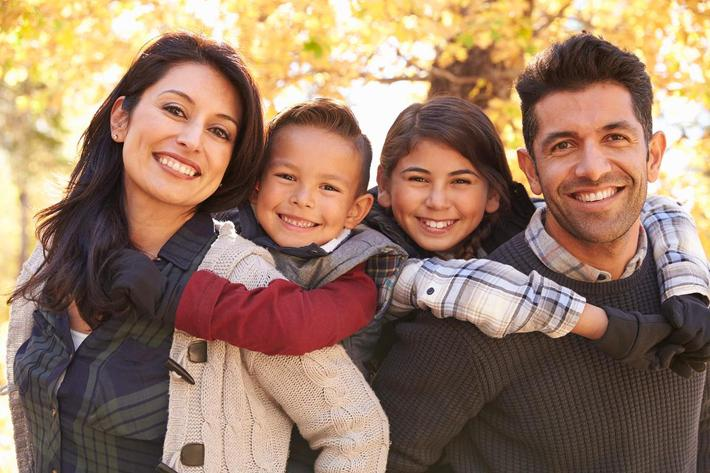 Portrait of happy parents piggybacking kids outdoors iStock-540095942.jpg