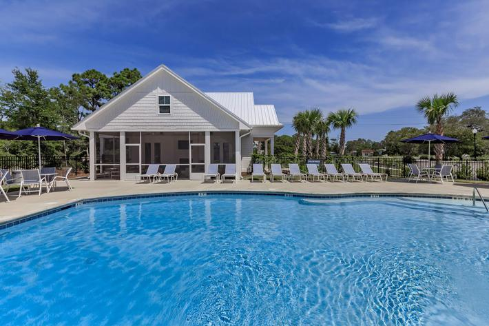 Soak up the sun at the shimmering swimming pool at The Townhomes at Beau Rivage in Wilmington, North Carolina.
