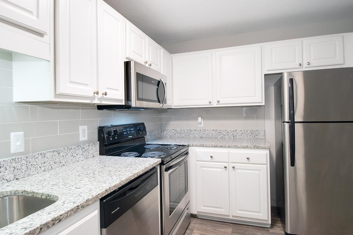 GRANITE COUNTERTOPS AND STAINLESS STEEL APPLIANCES IN KITCHEN