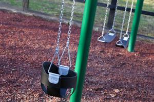 a swing set in front of a fence