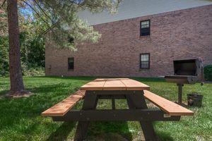 an empty park bench next to a brick building