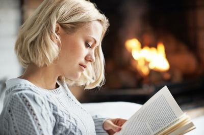 girl reading book by fire .jpg