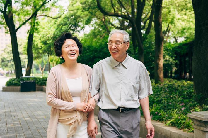 Senior-Asian-Couple-Walking-Trees-1160979740.jpg