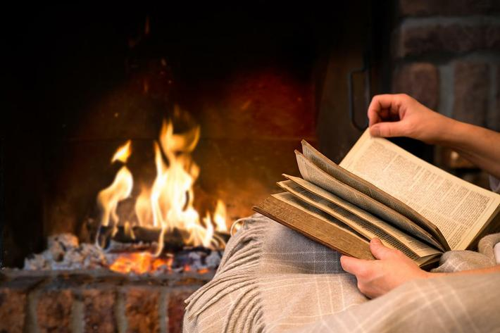 Reading book by fireplace iStock-475917291.jpg