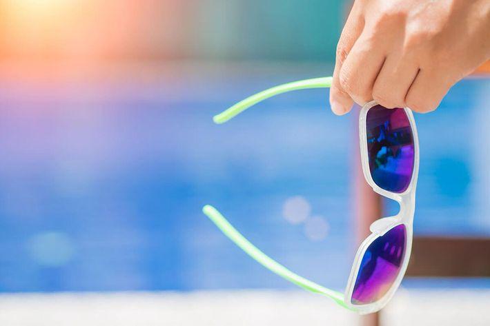 Woman hand holding sunglasses iStock-831868398.jpg