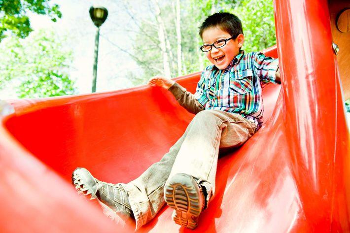 Happy boy on red slide iStock-182747708.jpg