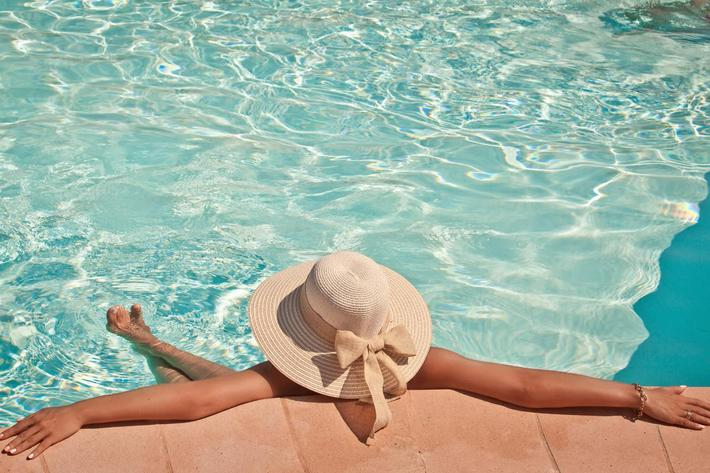 Woman in a pool hat relaxing in a blue pool iStock_000047226924_Full.jpg