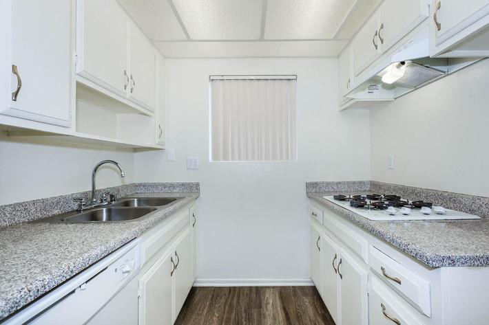 Unfurnished kitchen with white cabinets