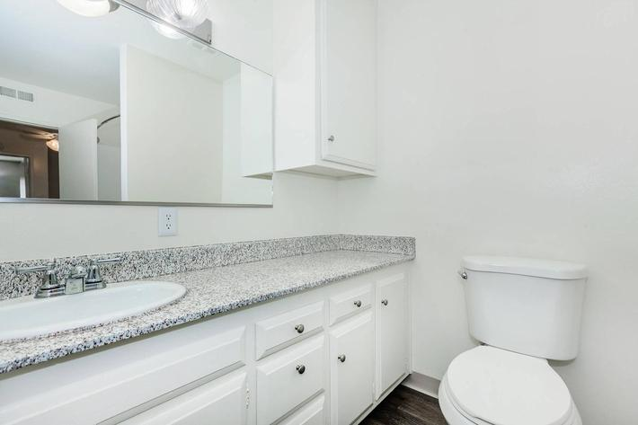 Vacant bathroom with white cabinets