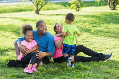 family-sitting-on-ground-in-park-iStock-618637194.jpg