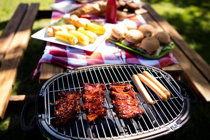 Barbeque with buns and corn on table in park GettyImages-808385052 copy.jpg
