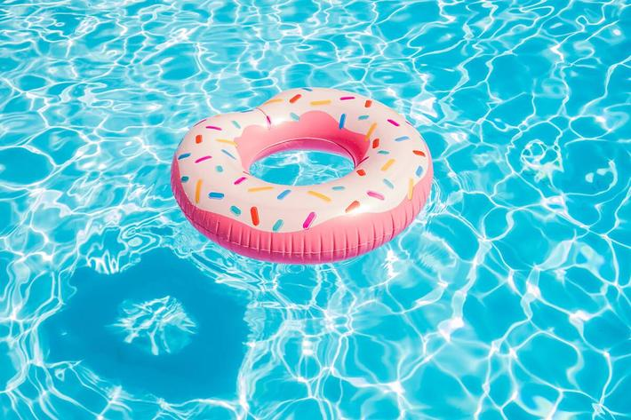 Pink inflatable donut swimming ring in a swimming pool iStock-853275074.jpg