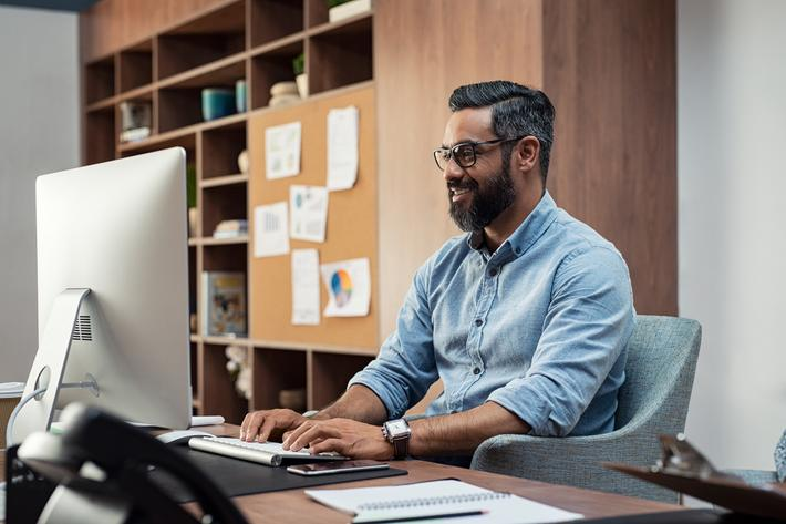 a man sitting at a desk in front of a computer