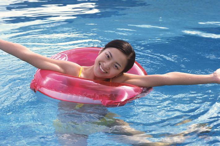 a young boy swimming in a body of water