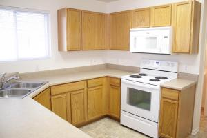 a kitchen with wooden cabinets and a microwave