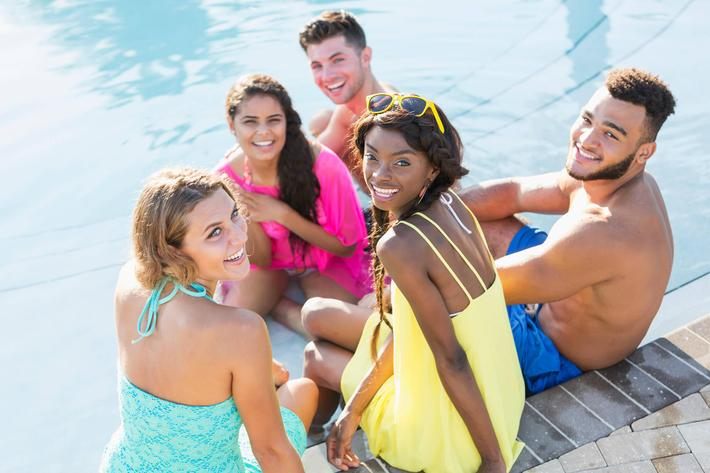 Multi-ethnic group of young adults sitting by swimming pool GettyImages-926384086.jpg
