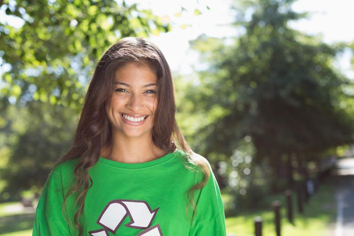 a girl smiling and wearing a green shirt