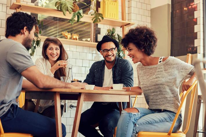 Cheerful young friends having fun in a cafe iStock_86713567_LARGE.jpg