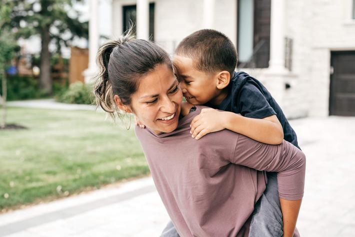 hispanic-mom-son-family-piggyback-hugging-1035146258.jpg