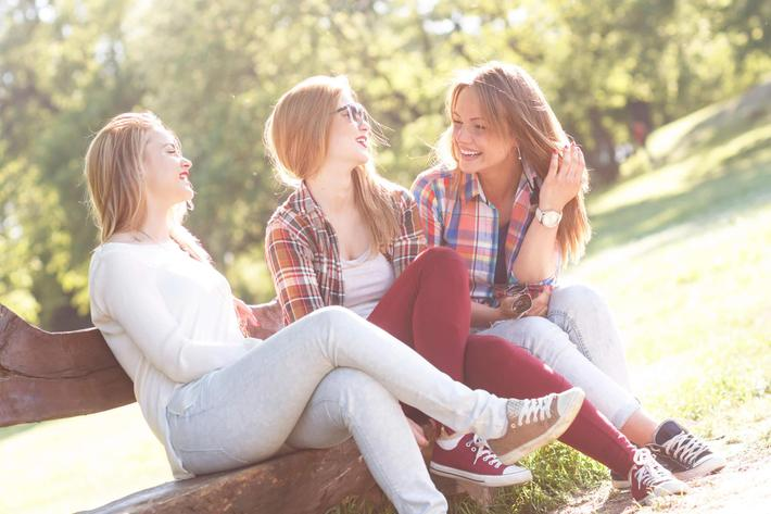 Three friends sitting on a park bench and chatting iStock_63573117_LARGE.jpg