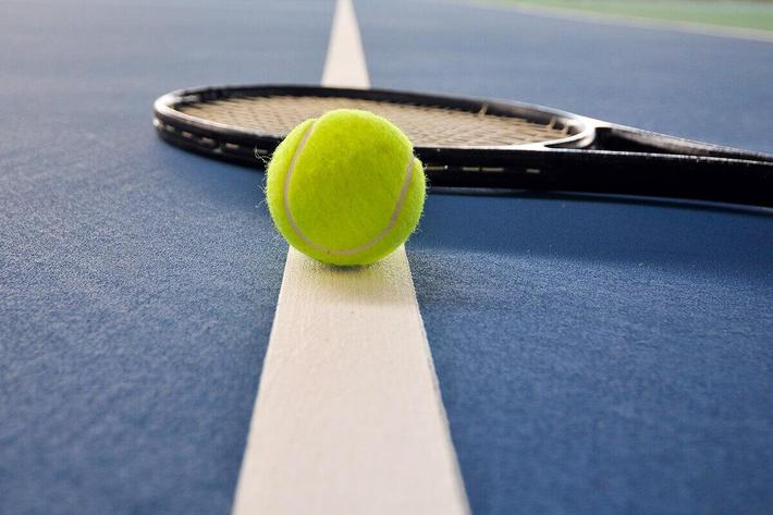Tennis ball and racket on the BLUE court iStock-146913330.jpg