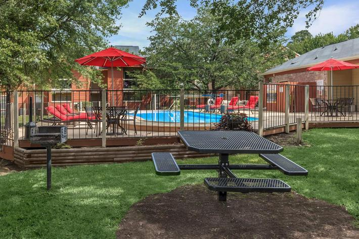 Picnic table - barbecue grill in grassy area by the pool
