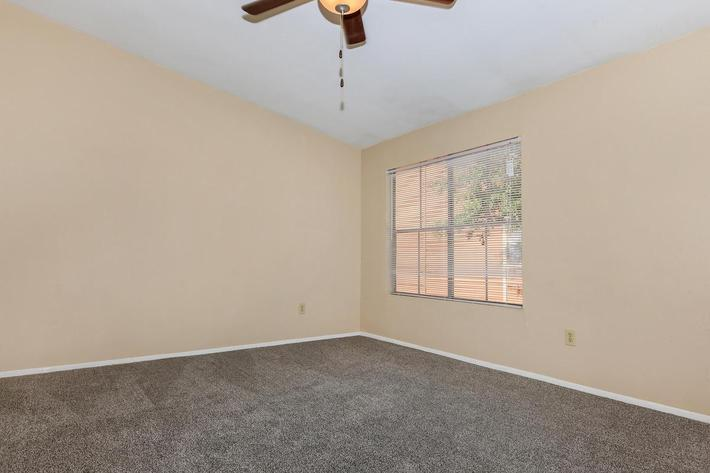 Large carpeted room with ceiling fan at The Park at Summerhill Road