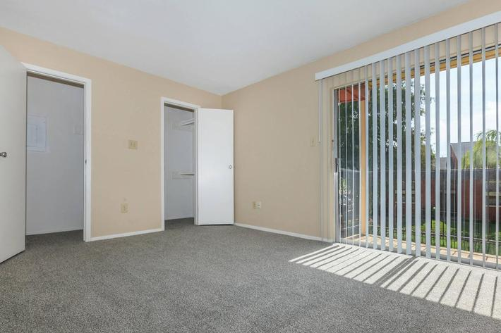 Spacious room with closet and large sliding glass door