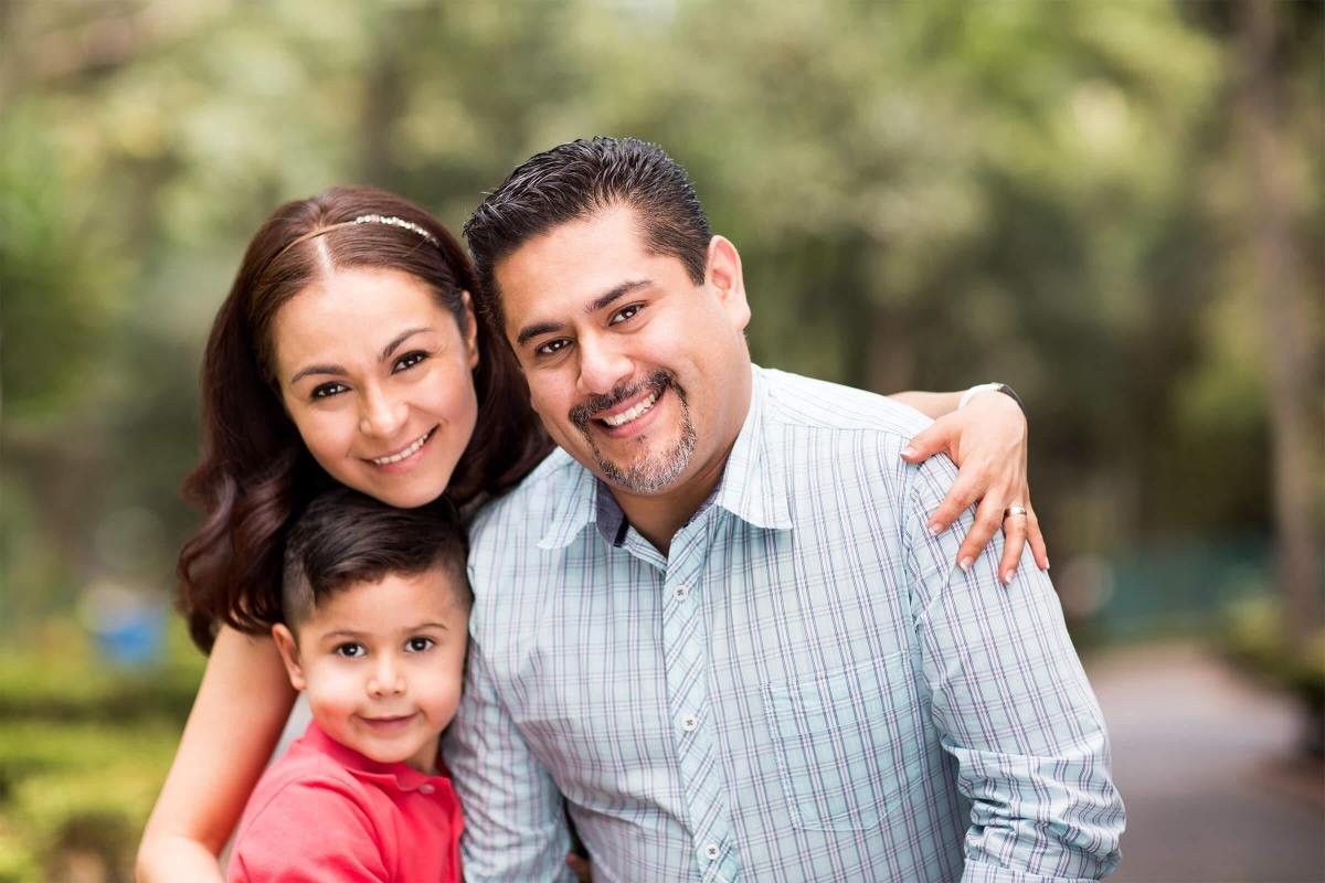 Happy latin family with one child smiling at camera iStock-617563858.jpg