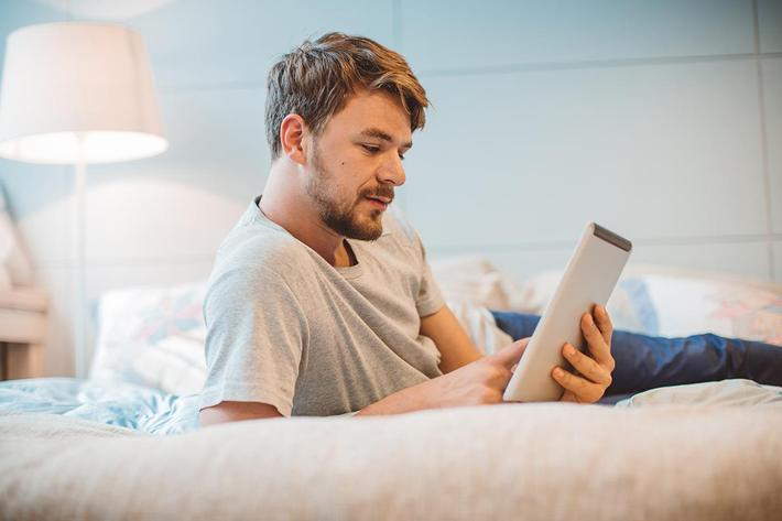 Young man enjoying reading at home.jpg