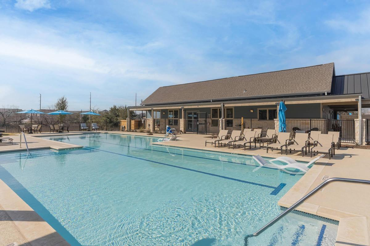 Senior Living in Pflugerville TX - Legacy Ranch at Dessau East Sparkling Pool with an Attached Clubhouse, Lounge Chairs, and Many More Amazing Community Amenities