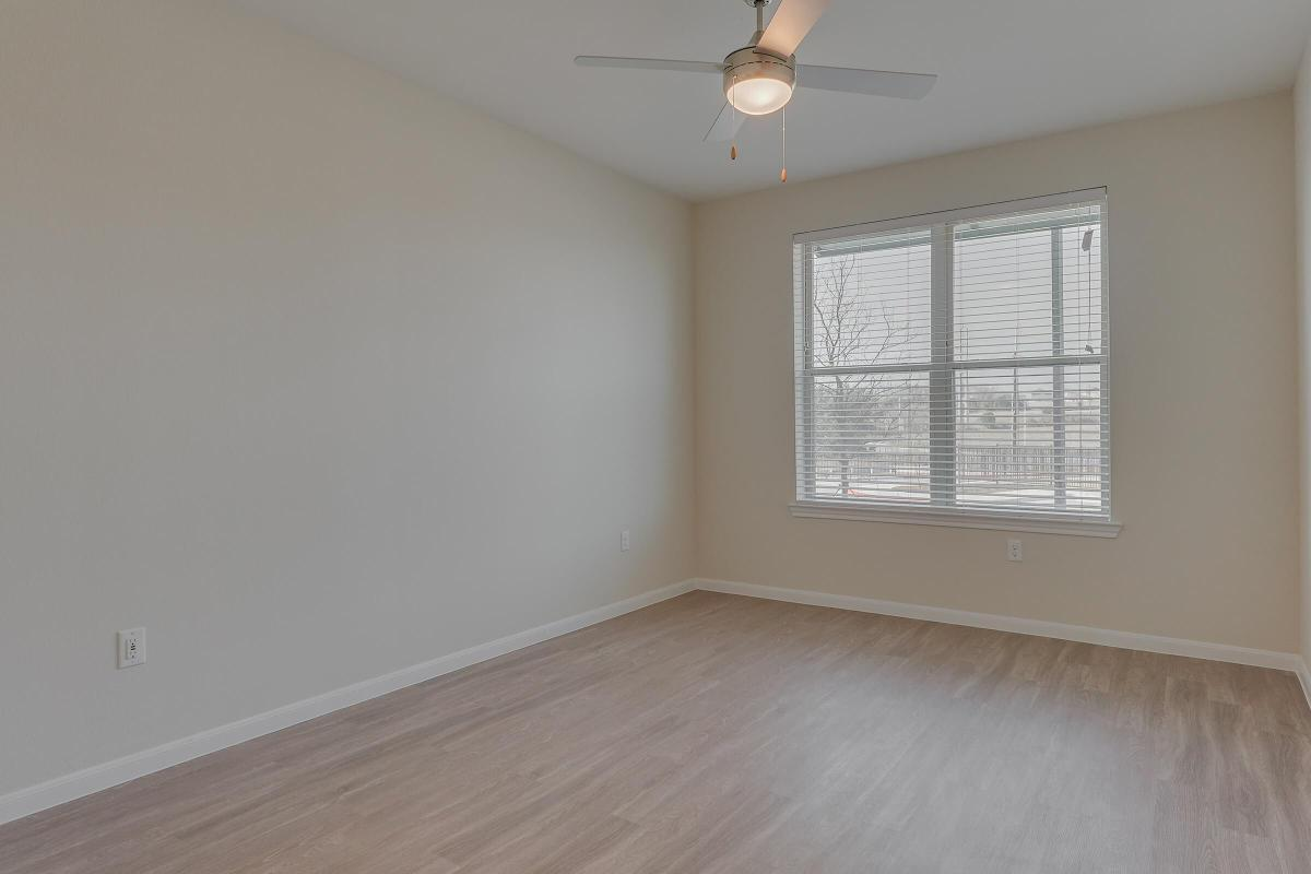 Apartments for Rent Pflugerville - Legacy Ranch at Dessau East Spacious Bedroom with a Expansive Closet, Wood-Style Flooring, and Many More Great Bedroom Amenities