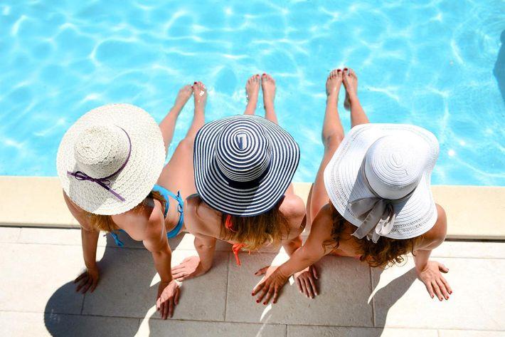 Young woman sun hat sitting poolside resort pool summer holiday iStock-636409474.jpg