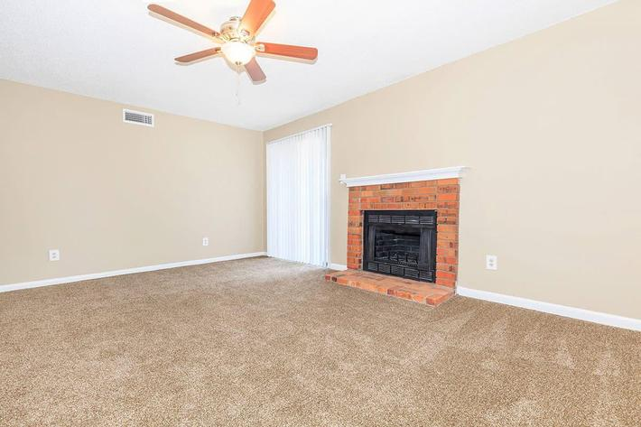 A BRICK FIREPLACE SITS IN THE LIVING ROOM OF AN APARTMENT AT VAN MARK APARTMENTS IN MONROE, LA
