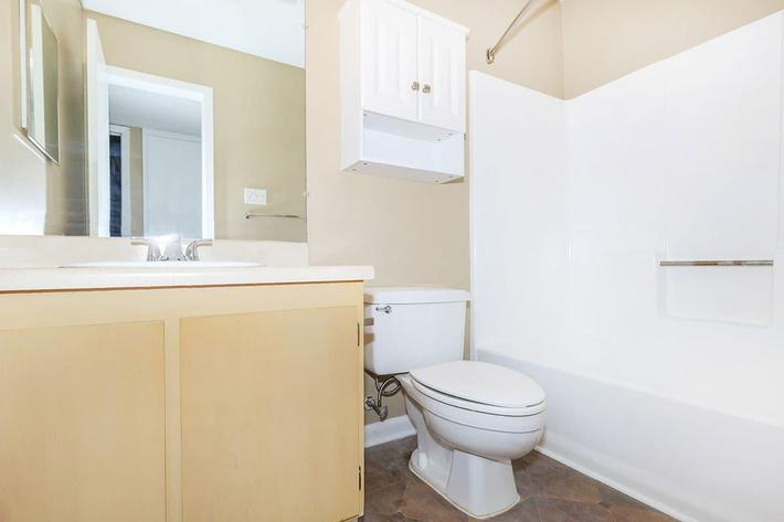 A SPOTLESS WHITE TOILET-SHOWER/BATH SITS ADJACENT TO A BEIGE CABINET IN A BATHROOM AT VAN MARK APARTMENTS IN MONROE, LA