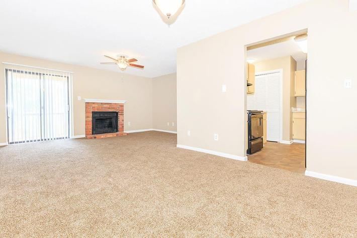 THE LIVING ROOM OF A 1-BEDROOM 1-BATHROOM APARTMENT INCLUDES A BRICK FIREPLACE AT VAN MARK APARTMENTS IN MONROE, LA115