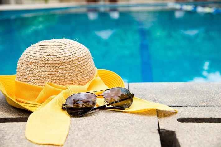 A SUN HAT-SUNGLASSES OF A RESIDENT SITS POOLSIDE FOR VAN MARK APARTMENTS IN MONROE, LA