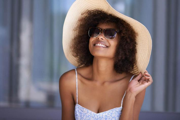 A YOUNG WOMAN WITH A LARGE SUN HAT-SUNGLASSES SMILES HAPPILY AT VAN MARK APARTMENTS IN MONROE, LA
