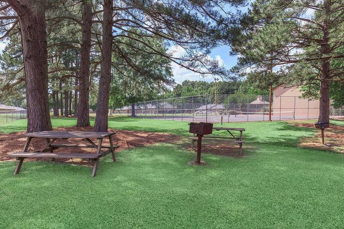 BARBECUES-PICNIC BENCHES SURROUND THE TENNIS COURT UNDER LARGE TREES AT VAN MARK APARTMENTS IN MONROE, LA