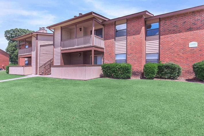 THE FINELY CUT LAWN SITS IN FRONT OF TWO APARTMENT BUILDINGS ON A BEAUTIFUL DAY AT VAN MARK APARTMENTS IN MONROE, LA