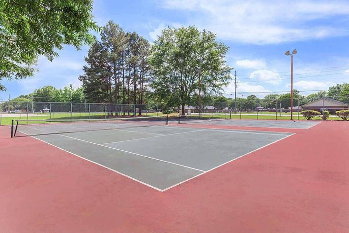 TWO RED-GREEN TENNIS COURTS SIT AVAILABLE FOR RESIDENTS AT VAN MARK APARTMENTS IN MONROE, LA