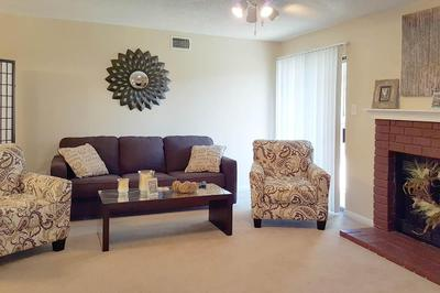 Two large chairs an a couch sit in front of a fireplace in a living room at the Van Mark Apartments
