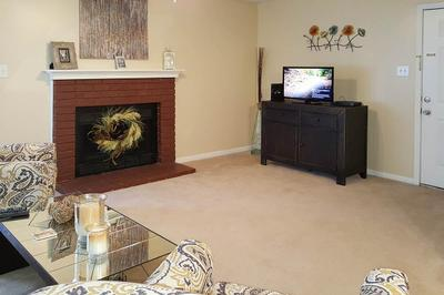 A tv faces two chairs and couch next to a fireplace in the living room at the Van Mark Apartments in