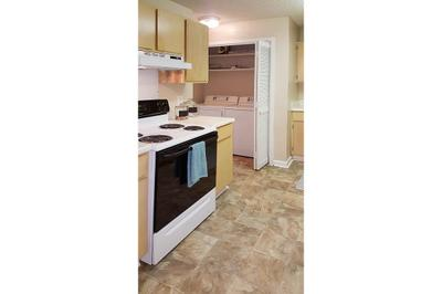 A washer and dryer sit hidden in the closet of a newly furnished kitchen at the Van Mark Apartments