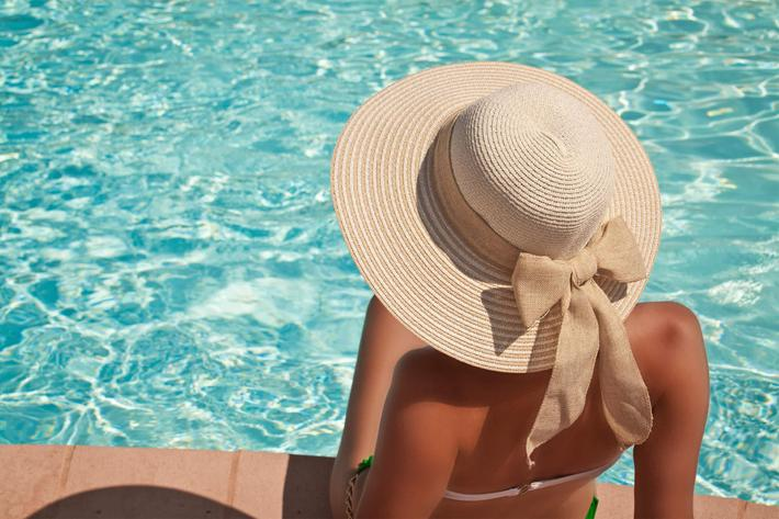 Young woman sitting on the ledge of the pool iStock_000047227562_Large.jpg
