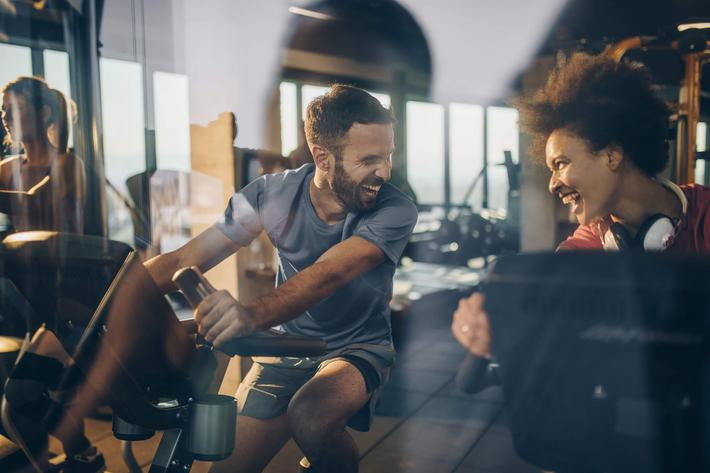 Happy athletes communicating and laughing while exercising in a gym together. iStock-860866680.jpg