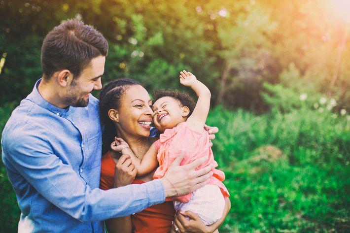 interracial-mixed-family-mom-dad-daughter-smiling-843909910.jpg