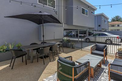 A spacious common area for Flats on Elk that has seating with and without umbrellas for shade.