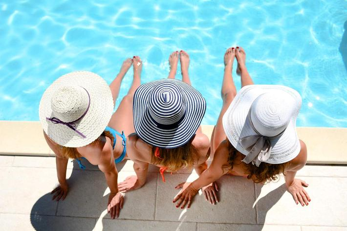 Young woman sun hat sitting poolside resort pool summer holiday iStock-636409474.jpg